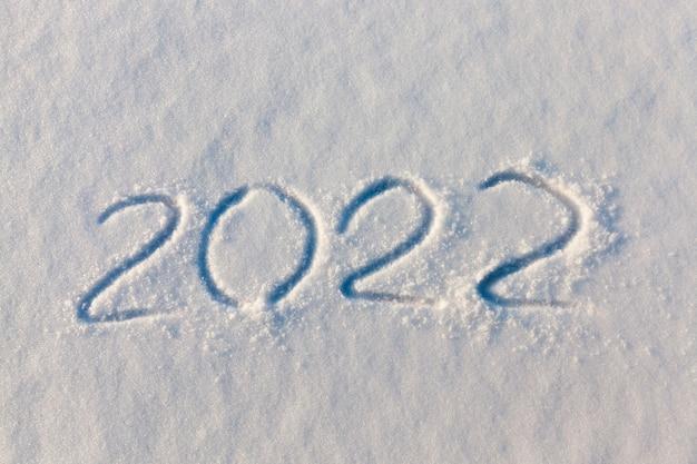 A inscrição sobre o ano novo de 2022 na neve no inverno, as inscrições sobre o ano novo, a temporada de inverno do final de 2021 e o início de 2022