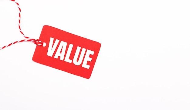 A inscrição value em uma etiqueta de preço vermelha sobre um fundo claro. conceito de publicidade. copie o espaço