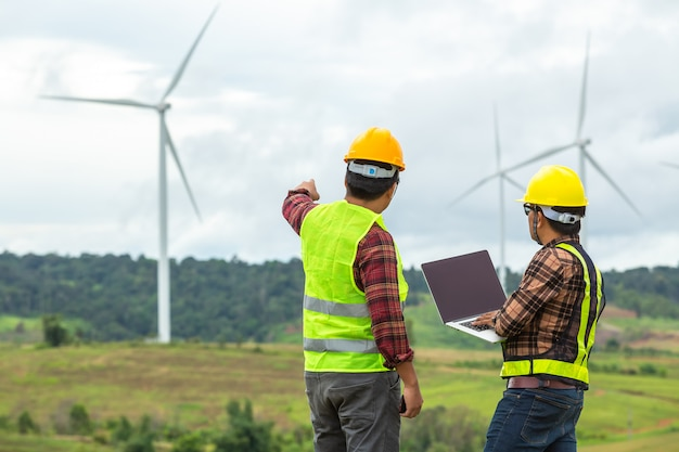 A inspeção do coordenador de dois moinhos de vento e o progresso verificam a turbina eólica no canteiro de obras.