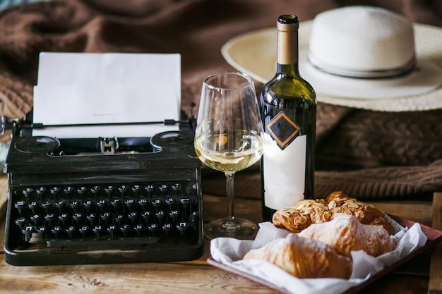 A inspiração de um escritor digitando textos em uma máquina de escrever vintage freelancer, croissants de café da manhã e vinho office no estilo loft