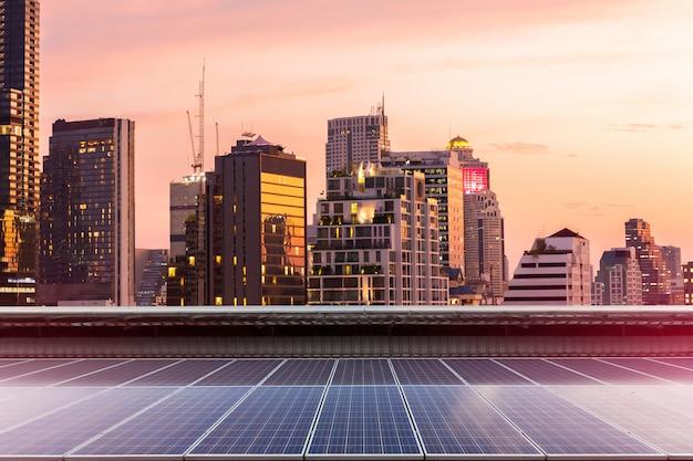 A instalação fotovoltaica do painel solar em um telhado da fábrica, fundo ensolarado do céu azul, fonte de eletricidade alternativa - conceito dos recursos sustentáveis.