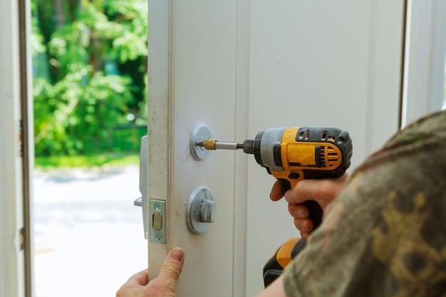 A instalação travou os puxadores da porta interiores, mãos do carpinteiro instalam a fechadura