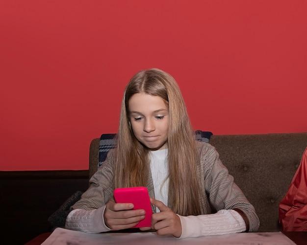 A internet. mensagem. menina em um café com um smartphone. a criança olha no smartphone. gadgets e crianças. um adolescente mantém seu videoblog. um blogueiro está olhando seu gadget.