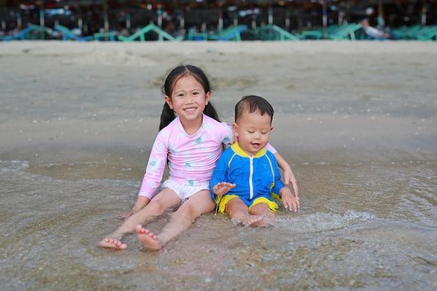 A irmã asiática pequena feliz e seu irmão mais novo no terno de natação que senta e que joga o mar acena na praia.
