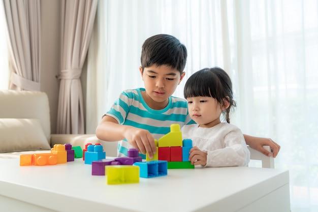A irmã e o irmão bonitos asiáticos jogam com um designer de blocos de brinquedo em cima da mesa na sala de estar em casa.