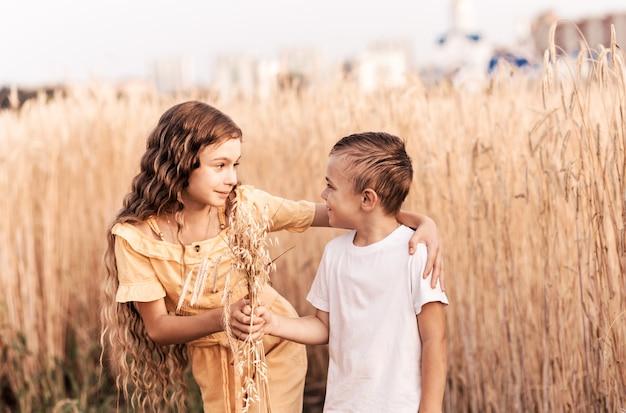 A irmã mais velha caminha com o irmão na natureza no verão. irmãos de crianças felizes andando e brincando. crianças brincam ao ar livre