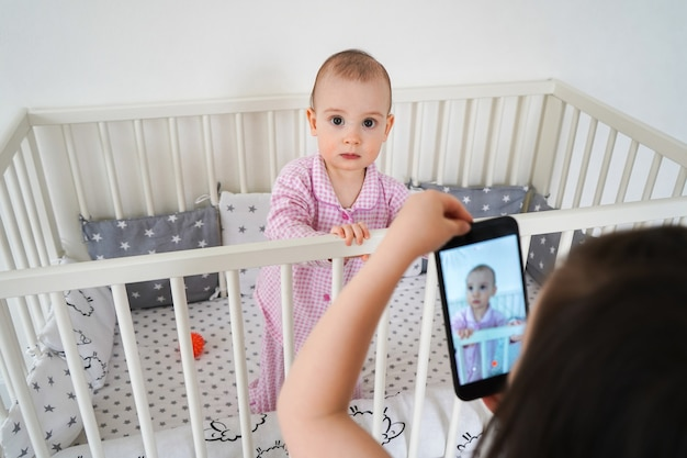 A irmã mais velha fotografa a mais nova em um smartphone. as crianças modernas usam dispositivos.