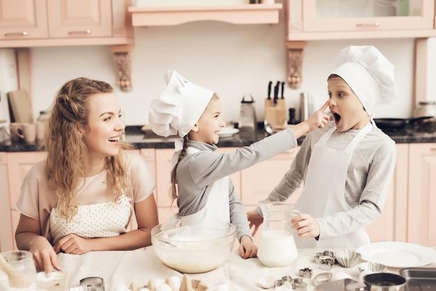 A irmã toca o dedo do nariz do irmão na farinha.