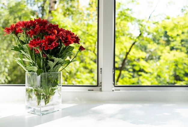 A janela é um vaso de vidro com crisântemos vermelhos.