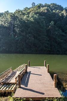 A jangada de bambu está flutuando perto do píer de madeira.