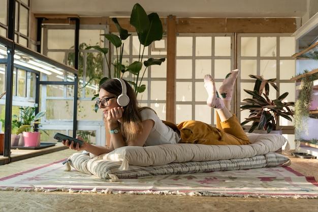 A jardineira relaxa depois do trabalho, deita na mensagem no chão no smartphone e ouve música para relaxar em casa