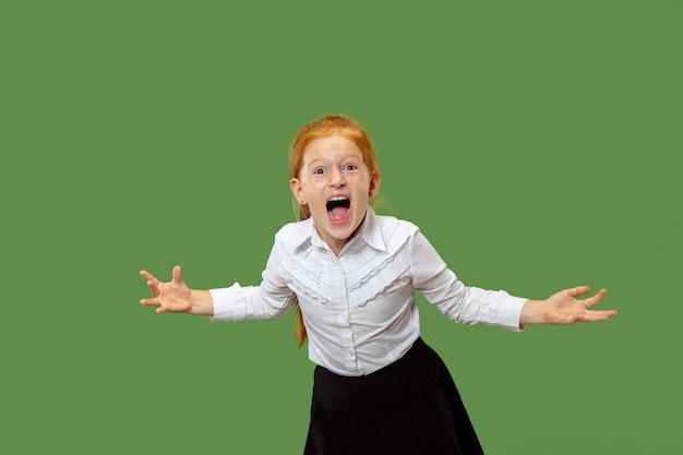 A jovem adolescente com raiva emocional gritando no fundo verde do estúdio
