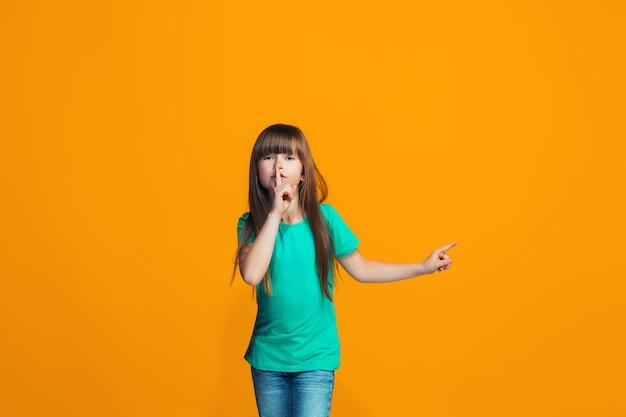 A jovem adolescente sussurrando um segredo atrás da mão sobre o espaço laranja