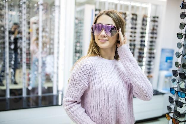 A jovem aluna está se preparando para estudar e experimenta novos óculos para seu visual perfeito na loja