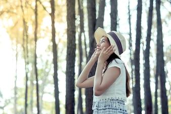 A jovem asiática colocou o chapéu e aproveitou a natureza no parque de pinheiros no tom de cor vintage