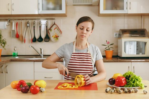 A jovem atraente de avental corta legumes para salada com uma faca na cozinha. conceito de dieta. estilo de vida saudável. cozinhando em casa. preparar comida.