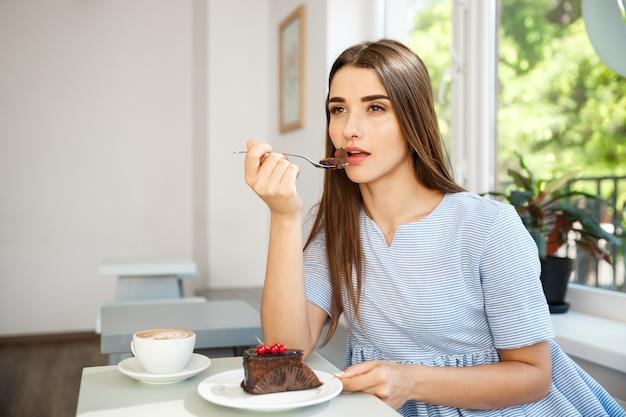 A jovem atraente mulher caucasiana gosta de comer bolo de chocolate com café quente na cafeteria moderna ao meio-dia.