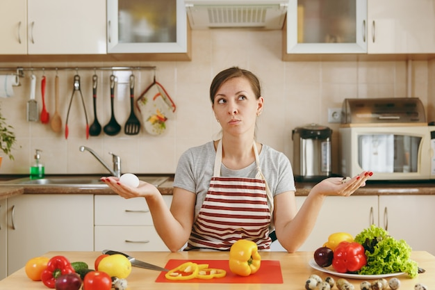 A jovem atraente mulher pensativa de avental escolhe entre ovos de galinha e de codorna na cozinha. conceito de dieta. estilo de vida saudável. cozinhando em casa. preparar comida.