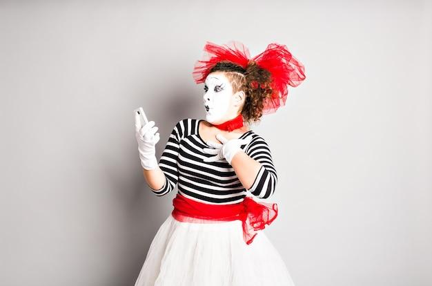 A jovem atriz está segurando um telefone celular e olhando para a tela com uma expressão de surpresa.