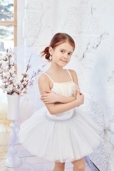 A jovem bailarina está se preparando para uma apresentação de balé. pequeno balé prima. menina em um vestido de baile branco e pointe perto da janela, lindo cabelo ruivo