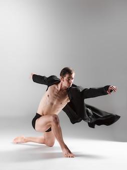 A jovem bailarina moderna atraente na parede branca