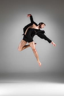A jovem bailarina moderna atraente saltando no fundo branco