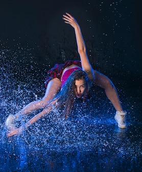 A jovem bailarina moderna linda dançando sob a água cai