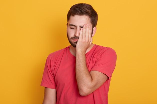 A jovem barba por fazer, exausta, metade do rosto com a mão em pé contra um estúdio amarelo, parece cansada, deprimida