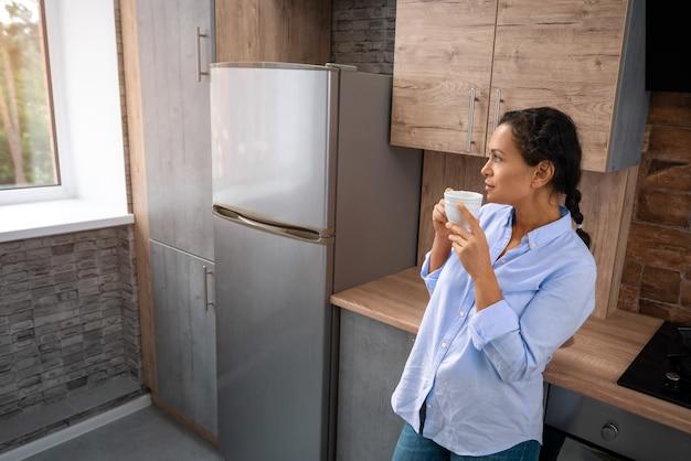 A jovem bebe café em pé na cozinha e olha pela janela.