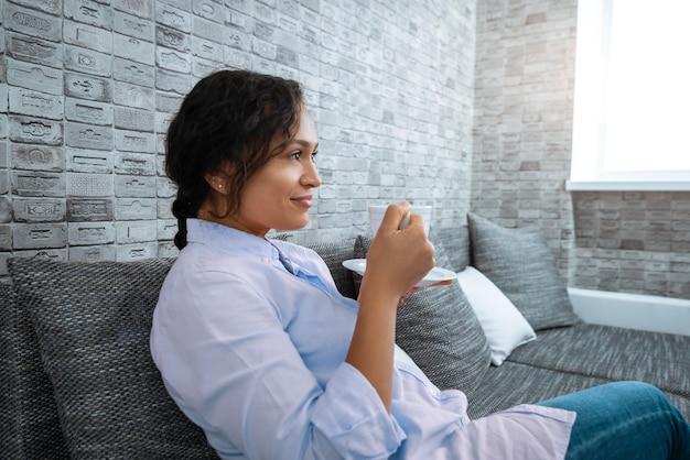 A jovem bebe café enquanto está sentada no sofá perto da janela.