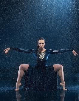 A jovem bela dançarina moderna dançando sob a água cai