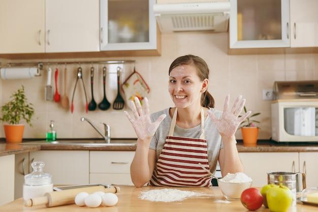 A jovem bela mulher feliz sentado à mesa com farinha e vai preparar um bolo na cozinha. cozinhando em casa. preparar comida.