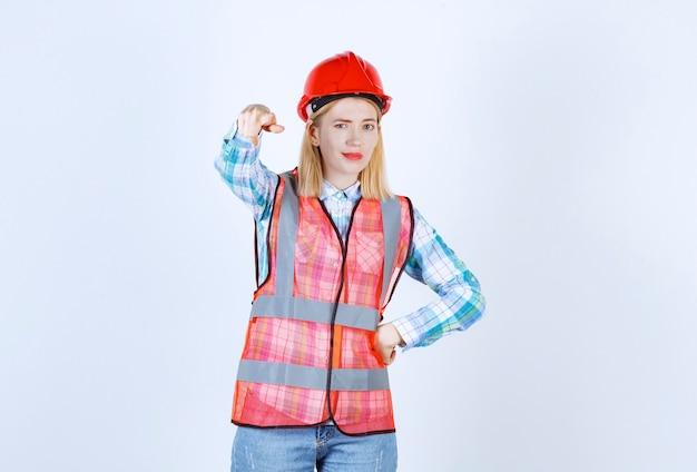 A jovem bonde está fazendo um sinal com a mão enquanto coloca a mão perto da cintura em frente à parede branca