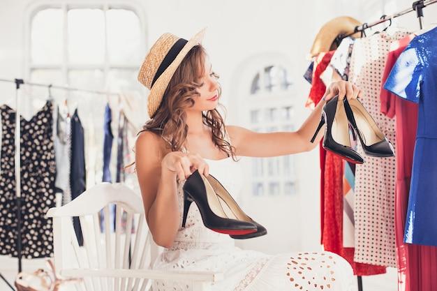 A jovem bonita escolhendo e experimentando sapatos modelo na loja