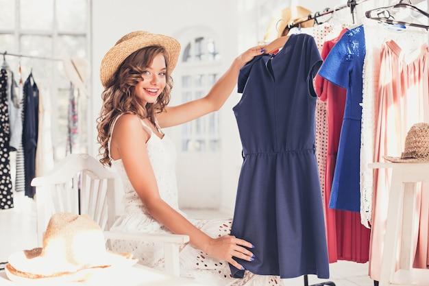 A jovem bonita escolhendo e experimentando vestidos na loja