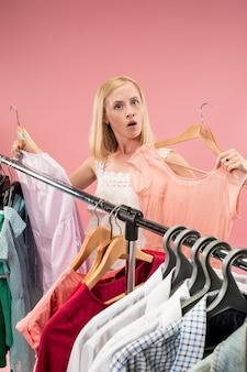 A jovem bonita olhando vestidos e experimentando enquanto escolhe na loja