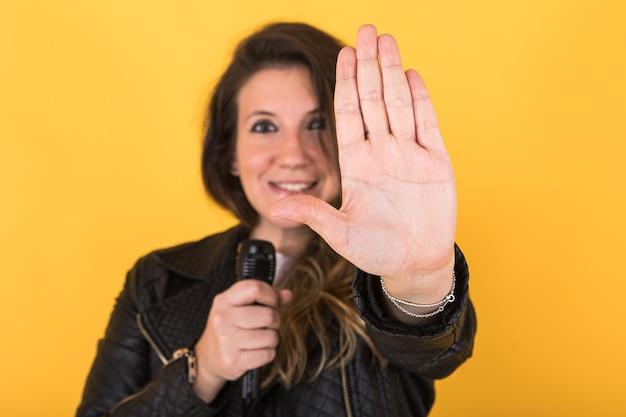 A jovem cantora, vestindo uma jaqueta de couro preta e um microfone fora de foco, faz o sinal de pare com a mão