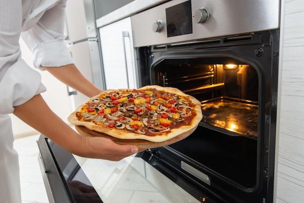A jovem chef tira uma pizza assada do forno em uma placa de madeira redonda.