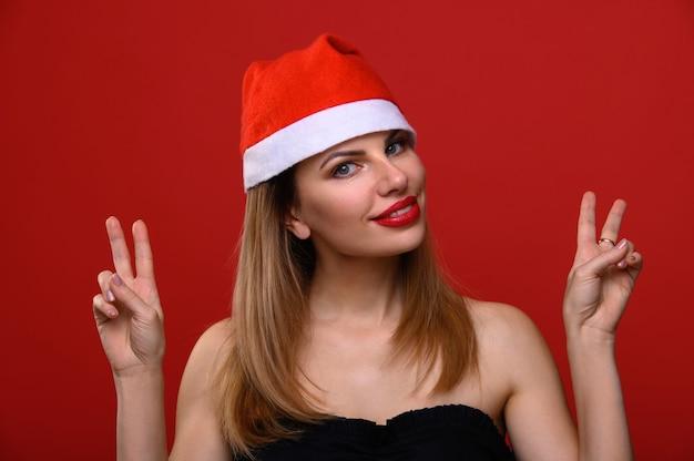 A jovem com um chapéu de papai noel sorri e faz aspas com as mãos