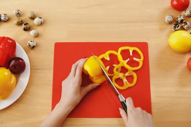 A jovem corta pimenta amarela para salada com uma faca na cozinha. conceito de dieta. estilo de vida saudável. cozinhando em casa. preparar comida. vista de cima.