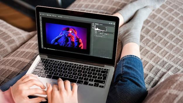 A jovem criadora de conteúdo está em seu laptop, sentada no sofá. trabalhando com fotos de casa