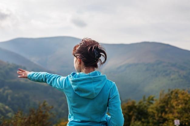 A jovem de pé no topo de uma montanha.