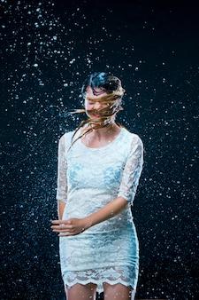 A jovem de pé sob água corrente
