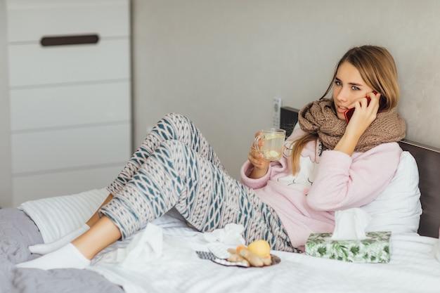 A jovem doente e infeliz deitada em uma cama