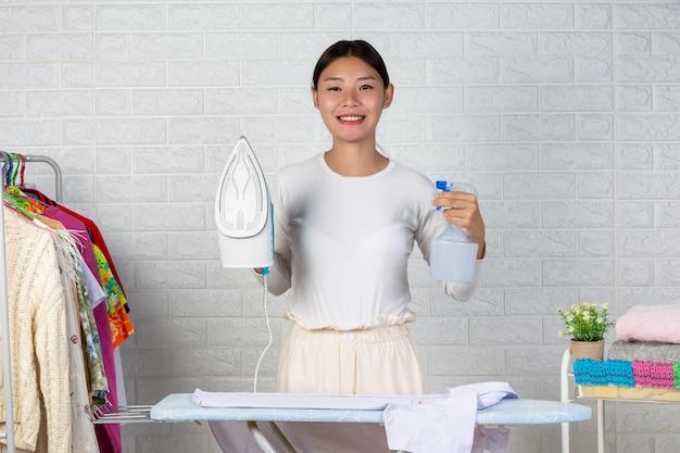 A jovem dona de casa que está satisfeita com seu ferro em um tijolo branco.