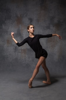 A jovem e bela dançarina de estilo moderno posando em um fundo cinza de estúdio