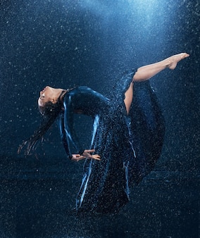 A jovem e bela dançarina moderna dançando sob as gotas de água