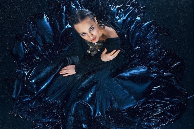 A jovem e bela dançarina moderna posando debaixo de gotas de água