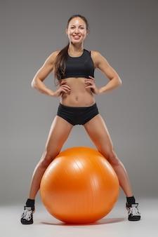 A jovem e bonita garota esportiva fazendo exercícios em um fitball