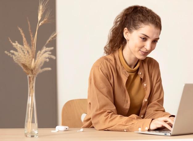 A jovem em seu espaço de trabalho sorri e trabalha